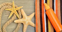 Starfish, color towel and sunscreen spray against. Stock Photos
