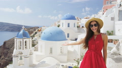 Woman presenting showing welcome gesture presenting you Oia Santorini Stock Footage