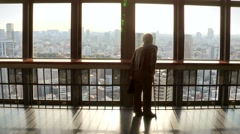 Older retired woman traveling and doing tourism on top skyscrapper floor. Stock Footage