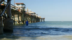 Man standing in water fishing under pier Stock Footage