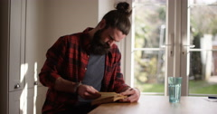 4k, Young man engrossed in reading a book at home. Stock Footage