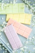 Composition with pastel colors chocolate bars, decorated with flowers - stock photo