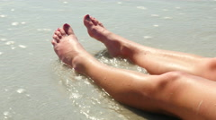Close up female legs with ocean waves Stock Footage