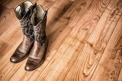 Old Cowboy Boots on Wood Floor - stock photo