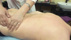 Masseuse make healing massage of back to young woman in saloon. Plucking - stock footage