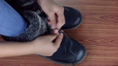 Close up of a little girl tying her winter boots. Stock Footage