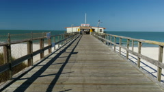 Long wooden pier at ocean with bird flying Stock Footage