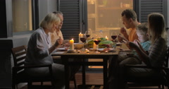 Big family having meal in late evening Stock Footage