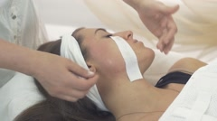 Cosmetologist removes waxing strip out cheeks of young girl in beauty saloon - stock footage