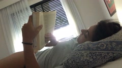 Girl reading a book in bed during afternoon Stock Footage