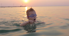 Kid learning to dive in the sea Stock Footage