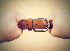 Two hands pulling a leather belt Stock Photos