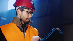 A young man in a helmet and overalls uses tablet Stock Footage