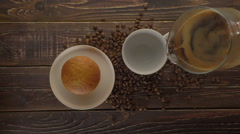man pouring hot coffee and milk into a cup on a dark wooden table, top view. - stock footage