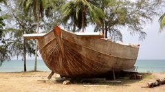 Hull of unfinished wooden boat with tropical palm trees & ocean Stock Footage