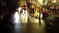 People crossing road in front of headlight beams Bangkok Erawan Shrine Stock Footage