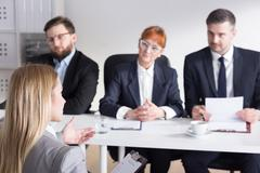Stock Photo of Three businesspeople during job interview with intern