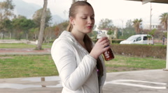 Young beautiful girl makes the drink a sip from the bottle and smiling Stock Footage