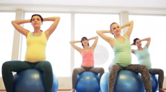 Happy pregnant women exercising on fitball in gym Stock Footage