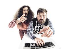 Two hilarious nerds staring at the monitor - stock photo