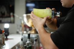 Bartender at work preparing cocktails. Shaking cocktail shaker Stock Photos