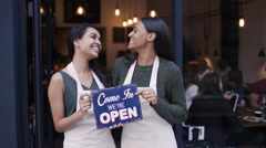 4K Happy women outside cafe hold up a sign to show they are open for business Stock Footage