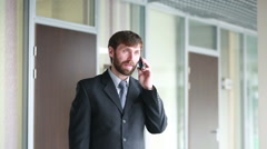 Successful business man having cell telephone conversation while standing in Stock Footage
