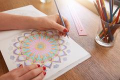 Woman hands drawing in adult colouring book Stock Photos