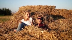 Girl lies on the hay and a young man jumping on a haystack and smiling. Stock Footage