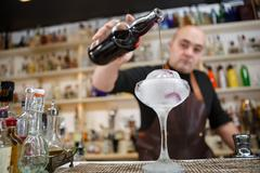 Bartender is pouring wine in the glass with giant ice, wide-angle image - stock photo