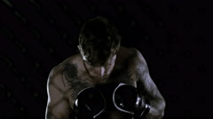 4K Muscular MMA fighter training alone in dark environment Stock Footage