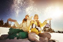 Two girls having fun tossing snow on sun backdrop Stock Photos