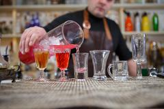 Bartender pours various of alcohol drink into small glasses on bar - stock photo