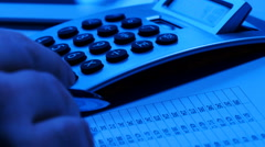 Man using calculator at desk, blue toned - stock footage