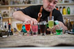 Bartender pours various of alcohol drink into small glasses on bar Kuvituskuvat
