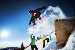 Snowboarder jumps from big rock on background of his friends when they have p - stock photo