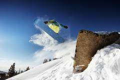 Snowboarder jumps from big rock. Sheregesh resort, Siberia, Russia - stock photo