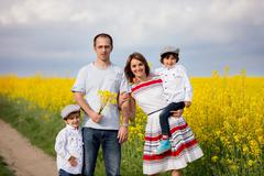 Family of four, mother, father and two boys, in a oilseed rape field Stock Photos