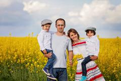 Family of four, mother, father and two boys, in a oilseed rape field - stock photo