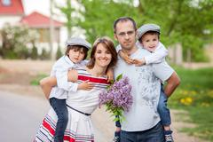 Family of four, mother, father and two boys, parent having the kids on piggy  - stock photo