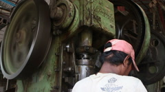 Metalworking Machine Shop - Lower angle huge metal stamping machine with worker Stock Footage