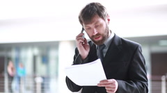 Mature Businessman Working With Papers And Cellphone At Workplace Stock Footage