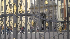 A view of some tourists and a few soldiers through a gate in the Prague Castle. - stock footage