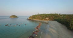 Aerial wide left sweep of kata beach longboats Stock Footage
