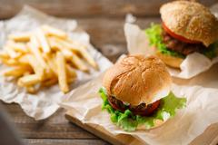 Homemade tasty burger and french fries on wooden table Stock Photos