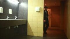 Businessman washing hands. Public toilet Stock Footage