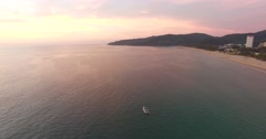 aerial pan - over ocean towards beach wedding photoshoot - stock footage