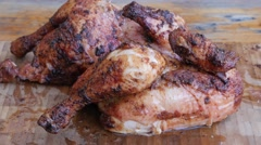 Slicing a grilled marinated chicken of the grill into peaces Stock Footage