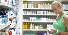 Woman choosing goods in beauty care section of store Stock Footage