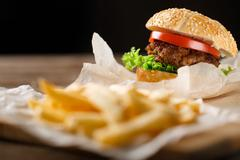 Homemade hamburgers and french fries on wooden table Stock Photos